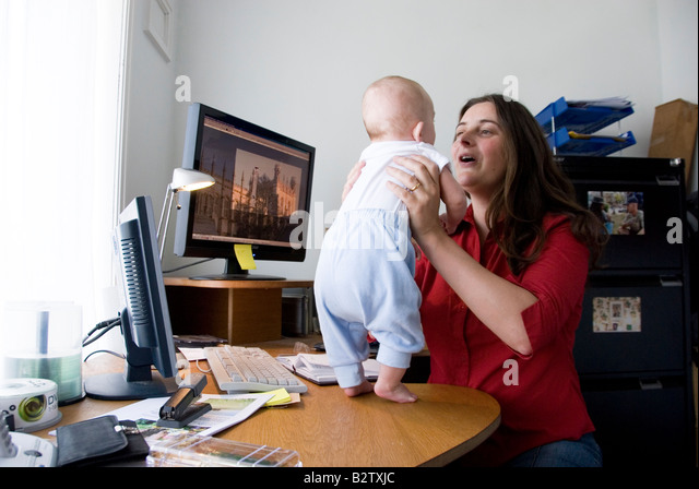home office multitasking. unique office multitasking woman working mother juggles work in home office and looking  after baby standing on her on