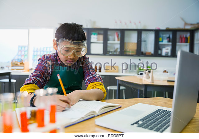 Elementary student writing in notebook stock photos