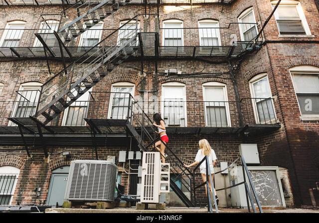 Apartment Building Fire Escape Ladder woman climbing ladder stock photos & woman climbing ladder stock