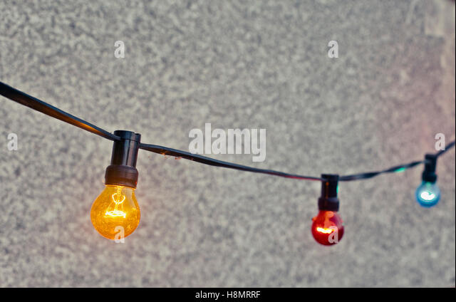 multi colored light bulbs hanging against wall stock image - Colored Light Bulbs
