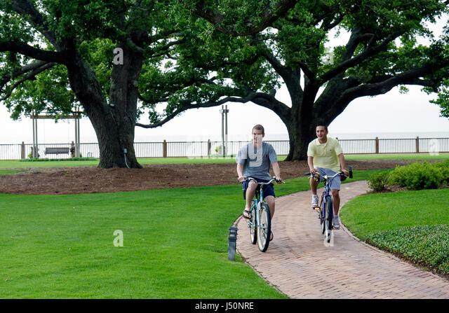 Point Clear Alabama Grand Hotel Marriott Resort hotel lodging Mobile Bay live oak man men bicycles - Stock Image