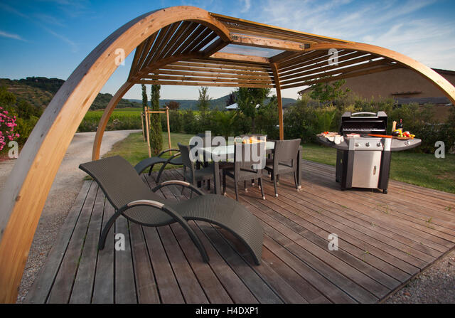 Equipment To Do The Barbecue With Grill And Portable Fire Under A Pergola  In The Shade