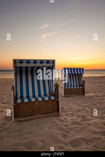Two beach chairs at North Sea beach of Hornum, Sylt, in sunset - Stock Image