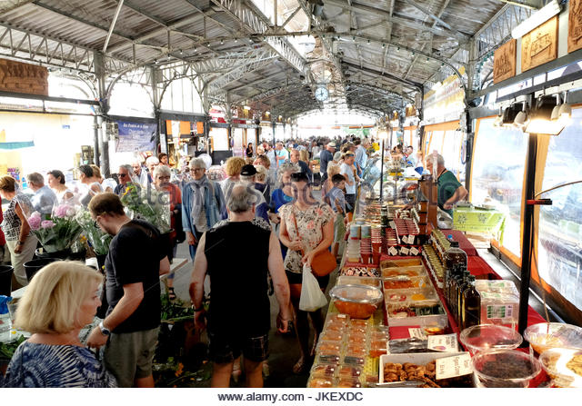 A busy Saturday morning market day scene in Antibes, France. residents and tourists jostle among the fresh, locally - Stock Image