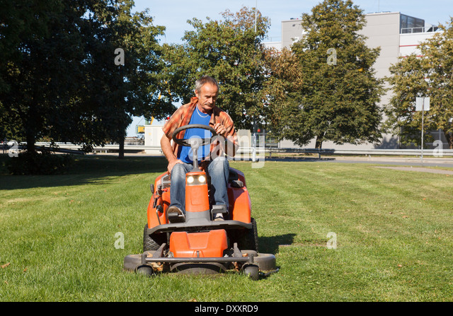 Man On Tractor Lawn Enforcment : Driving lawnmower stock photos