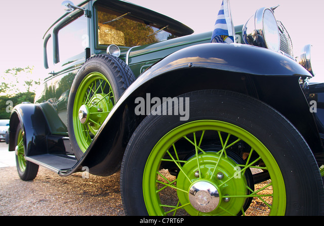 view on front wheel of green classic car stock image