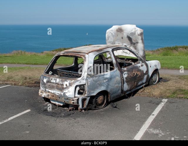 burnt out car abandoned in seaside car park yorkshire uk stock image