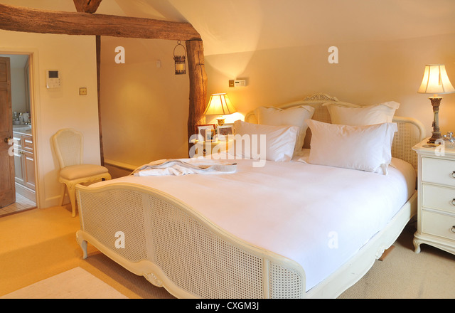 The interior designed bedroom of an english cottage with bed  bedside  cabinets  lights. English Cottage Interior Stock Photos   English Cottage Interior