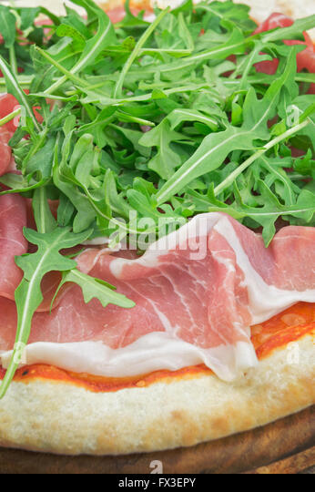 Pizza With Salad Rocket And Ham On Wooden Plate Stock Image