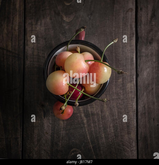 Freshly picked cherries on dark wooden table, from above - Stock Image