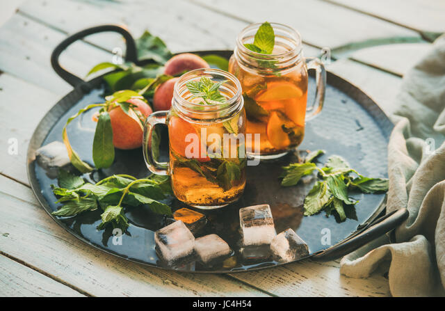 Summer refreshing cold peach ice tea on rustic wooden table - Stock Image