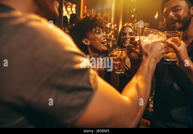 Happy group of people enjoying drinks at bar. Young friends at nightclub toasting cocktails. - Stock Image
