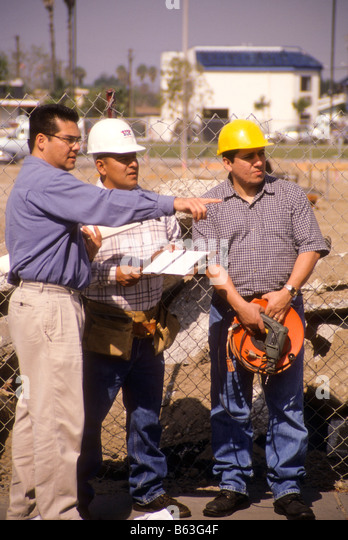 Hispanic Engineer Talks With Construction Workers On Building Project