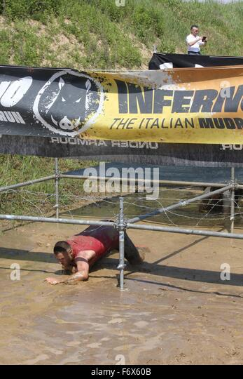 Signa Italy  City pictures : SIGNA, ITALY MAY 9 2015: Man passing under the wires in a mud ground ...