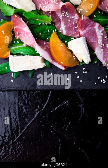 Salad with ham jamon serrano, camembert, melon, arugula on black stone slate plate on black background. Top view. - Stock Image