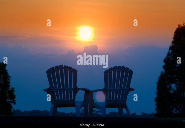 Adirondack Style Chairs Silhouetted At Sunset   Stock Image