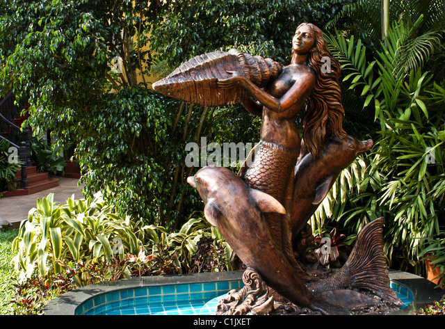 Bronze Statues Of Dolphins With A Mermaid Holding Large Seashell Trapped In  A Pond Of Water