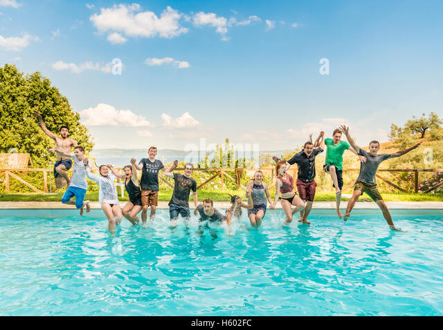 group of teenagers teens jumping in pool lazio italy   stock image