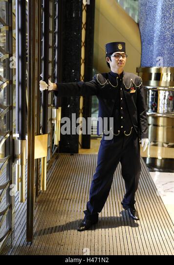 Man doorkeeper hotel door Macau China - Stock Image