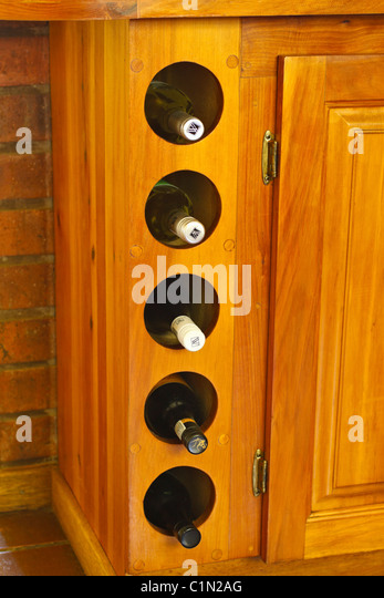 vertical wine rack as part of fitted wooden kitchen cupboards stock image