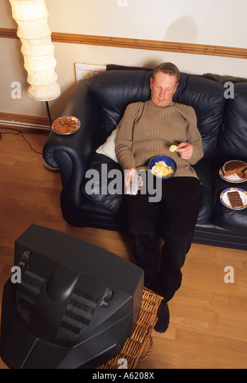 man sat on setee surrounded by junk food in front of the television holding remote controller