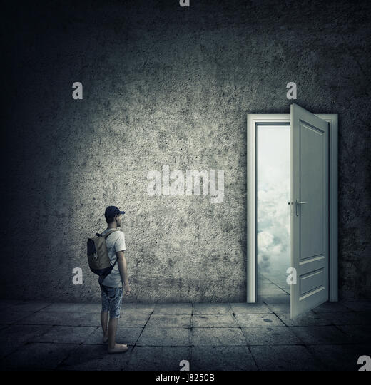 Abstract idea with a person standing in a dark room, in front of a opened door. Escape opportunity, entrance to - Stock Image