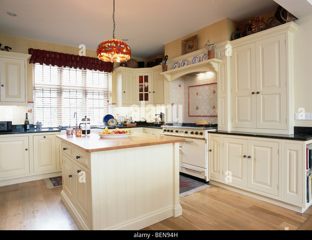 Cream Fitted Cupboards And Units In Country Kitchen With Island Unit Stock Image