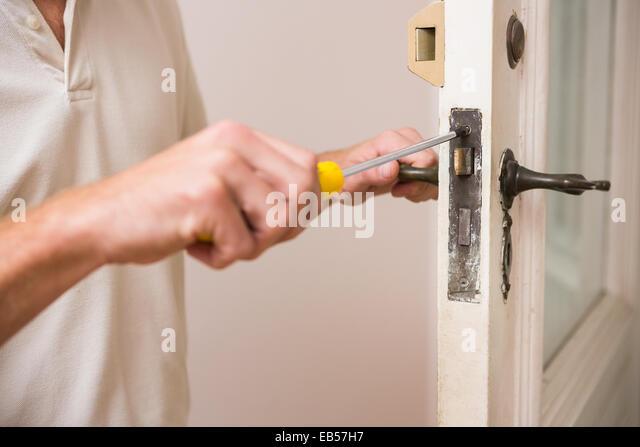 Man fixing the door handle with screwdriver - Stock Image & Man Fixing Door Stock Photos u0026 Man Fixing Door Stock Images - Alamy pezcame.com