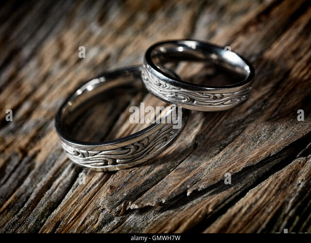 two white gold wedding rings with celtic design on rustic wood background artistic still life - Pagan Wedding Rings