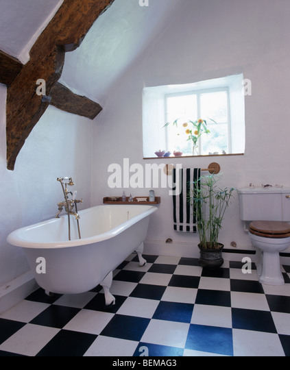 Roll-top bath and black+white chequer-board vinyl flooring in white attic