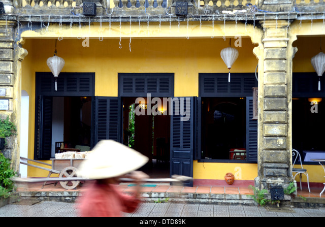 Local In Non La Traditional Hat Against French Colonial Architecture Hoi An Vietnam
