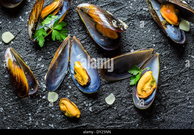 Fresh mussels cooking with parsley and garlic - Stock Image