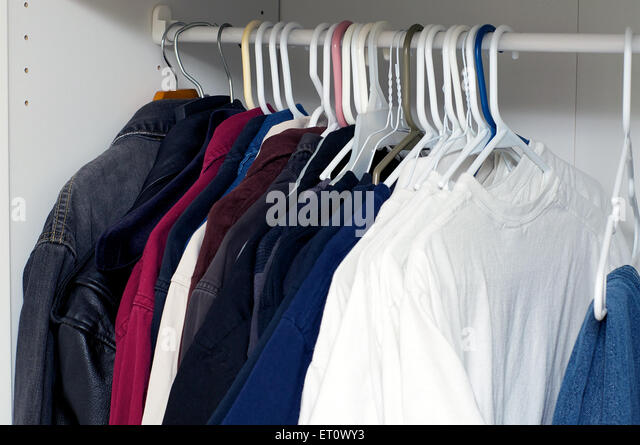 Looking Inside A Manu0027s Closet Or Armoire Full Of Clothes Hanging On  Hangers.   Stock