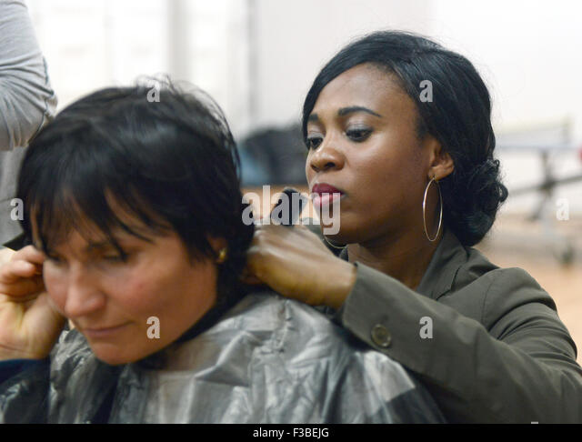 Duesseldorf, Germany. 4th Oct, 2015. Hairdresser Nancy (r) cuts the