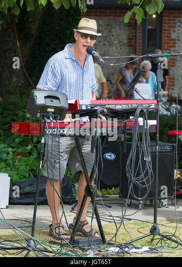 Man in a music band standing outside playing the keyboard. - Stock Image