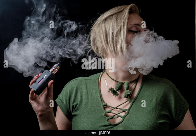 Young adult female exhaling smoke clouds from electronic cigarette - Stock Image