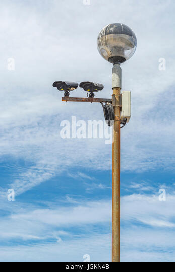 Two CCTV surveillance cameras mounted on a lamp post - metaphor for 'big brother is watching you' concept, - Stock Image