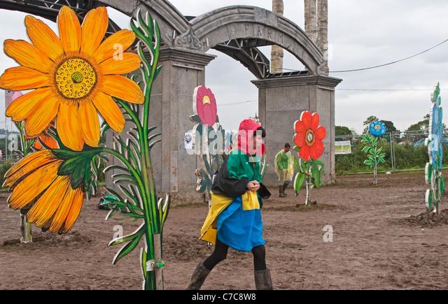 Visitors Walk Through The Mud At Glastonbury Festivals Park