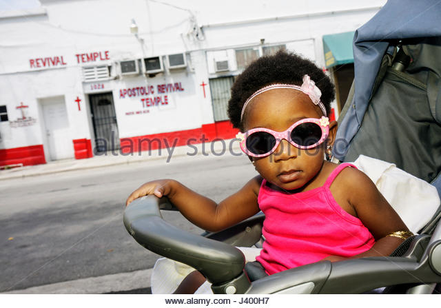 Miami Florida Overtown Black girl baby toddler stroller pink sunglasses hair bow revival temple fashion - Stock Image