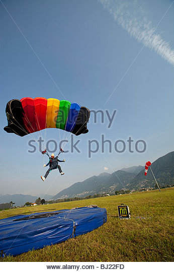 A Skydiver With An Open Parachute Just Before The Landing On Mat