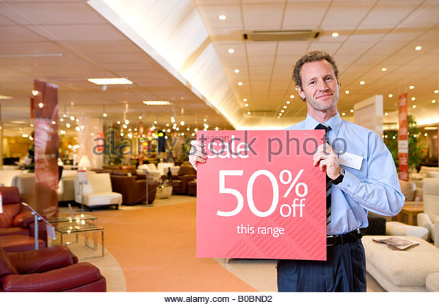 Salesman with  sale  sign in furniture shop  smiling  portrait   Stock Image. Furniture Shop Sale Stock Photos   Furniture Shop Sale Stock