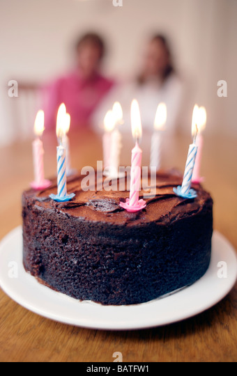 Birthday cake with lit candles. - Stock Image