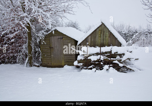 snow covered wooden garden sheds hampshire england stock image