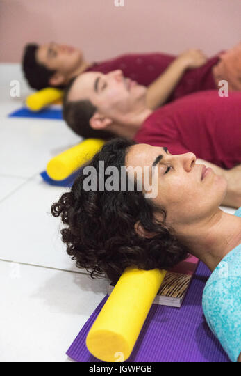 People at yoga class resting head on block - Stock Image