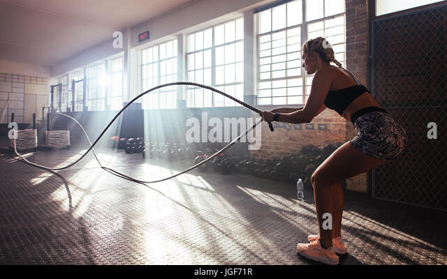 Woman lifting heavy weights at the gym for muscle training. Athlete exercising using a weight bar. - Stock Image