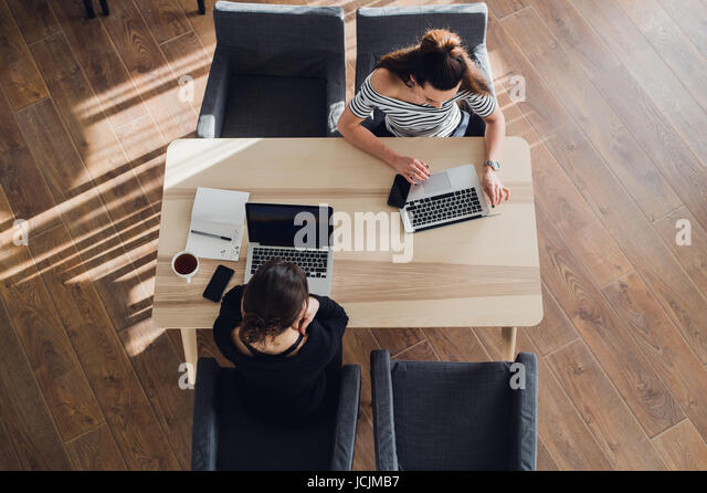 startup business and new mobile technology concept with young couple in modern bright office interior working on - Stock Image