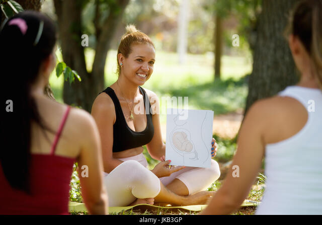 Pregnant women taking prenatal lesson in park. Teacher explaining baby growth inside belly with pictures and drawings. - Stock Image