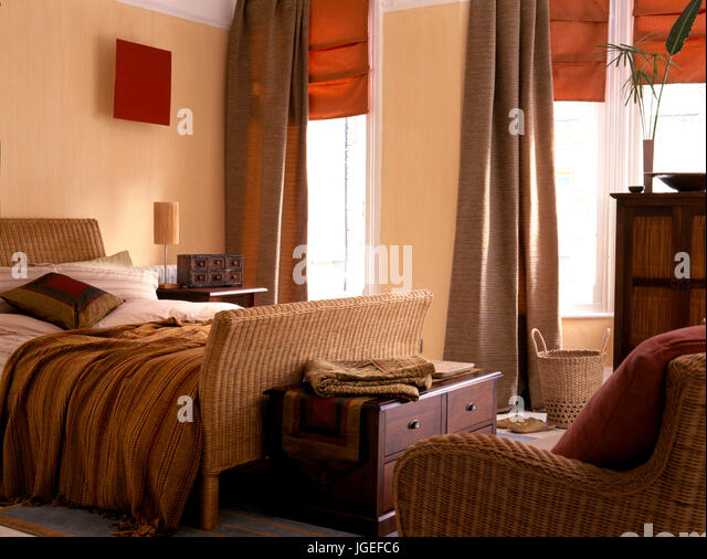 wicker bed in bedroom with orange blinds and brown drapes stock image - Drapes And Blinds