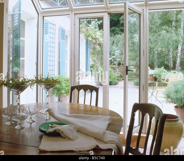 Chairs And Circular Table In Conservatory Dining Room With French Doors Open To Garden