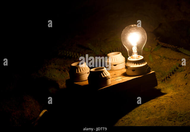 one lightbulb out of four other. A metaphor of the right decision. - Stock Image